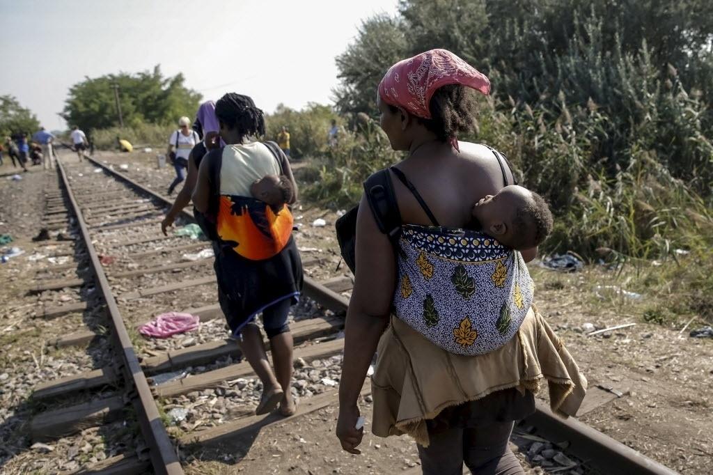 21.abr.2016 - Imigrantes carregam bebês nas costas enquanto caminham por linha de trem próxima a aldeia de Horgos, na Sérvia, em direção à fronteira com a Hungria. Milhares de refugiados, na sua maioria que fogem da guerra na Síria ou da pobreza na África, tentam cruzar a Europa em busca de uma vida melhor. No entanto, constantemente são impedidos por barrerias criadas por alguns países