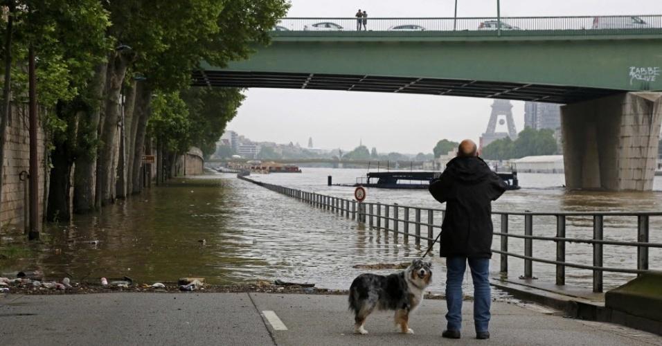 2.jun.2016 - Um homem anda com seu cachorro e tira foto em frente as águas do rio Sena, em Paris, que transbordou após dias de chuva. o rio atinge o maior nível dos últimos 30 anos e a previsão é que a água suba ainda mais