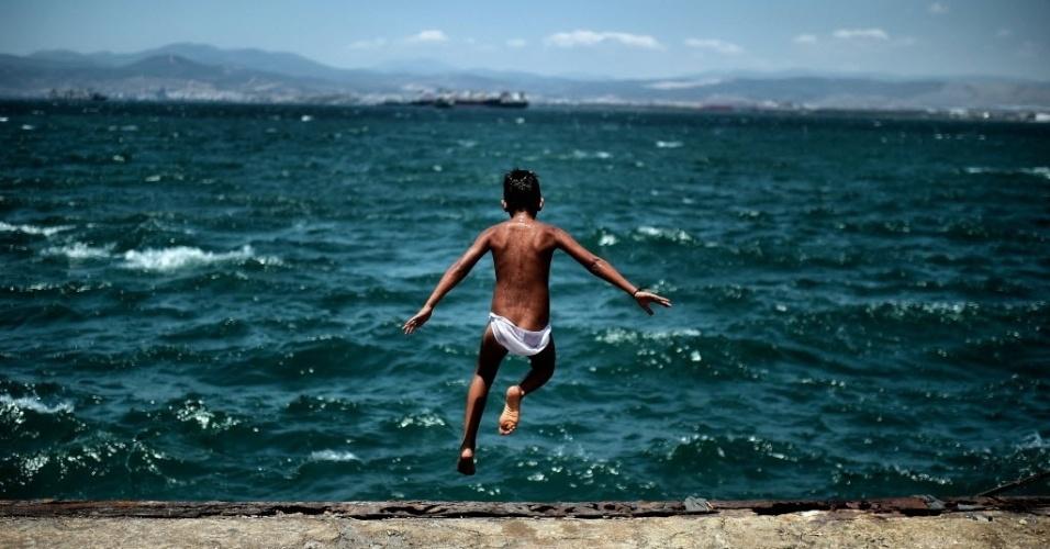 24.jun.2016 - Jovem salta no mar ao lado de um campo de refugiados em Skaramangas, Atenas, na Grécia. Mais de 800 mil imigrantes que fogem de guerras, perseguições e dificuldades do Oriente Médio e da Ásia desembarcaram nas ilhas gregas