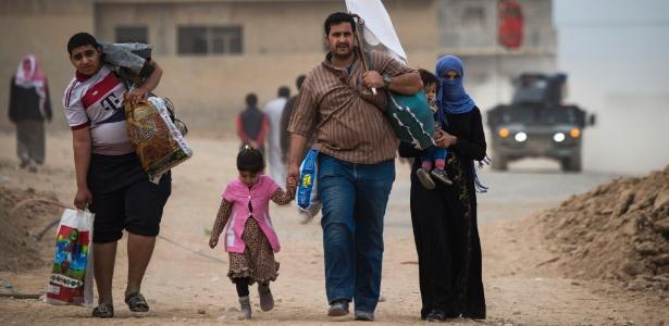 """Família iraquiana carrega bandeira branca sinalizando """"paz"""" ao deixarem área que estava sob controle do Estado Islâmico em Mossul"""