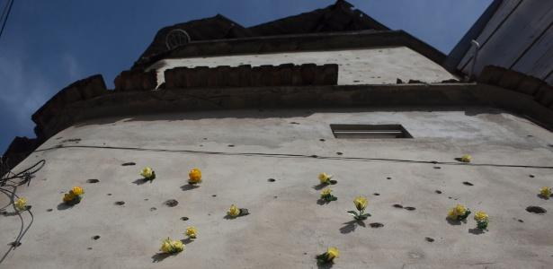 Na linha de tiro, fachada de casa crivada de balas tem camada extra de cimento na Maré
