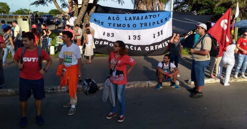 Torcedores gremistas se manifestam antes do julgamento do ex-presidente Lula em Porto Alegre; na faixa, fazem piada com o apartamento do qual Lula seria dono, fazendo menção às conquistas do clube na Copa Libertadores (1983, 1995 e 2017)