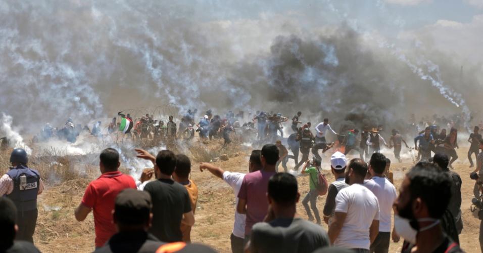 14.mai.2018 - Palestinos correm de bombas de gás lacrimogênio atiradas por forças israelenses durante confrontos na Faixa de Gaza