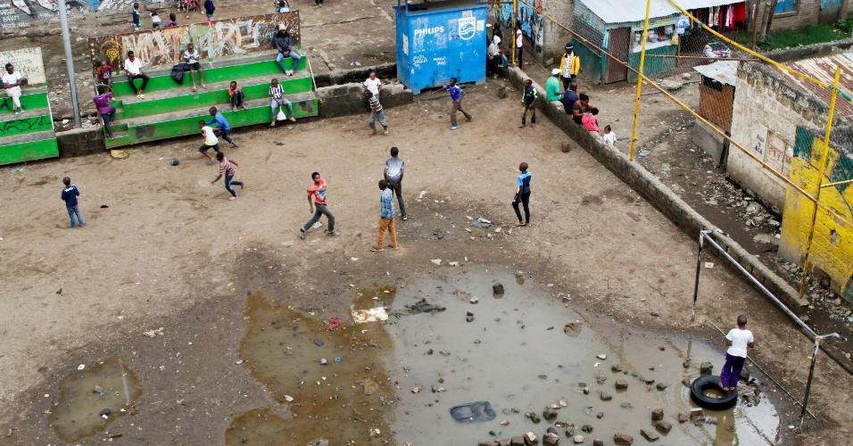 1.maio.2018 - Meninos jogam futebol em uma quadra alagada perto do vale de Mathare, em Nairóbi, no Quênia
