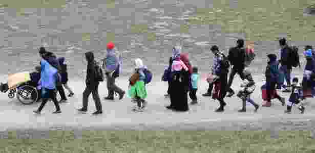 Migrantes caminham ao posto da polícia federal alemã após passar pela fronteira entre Áustria e Alemanha - CHRISTOF STACHE/AFP
