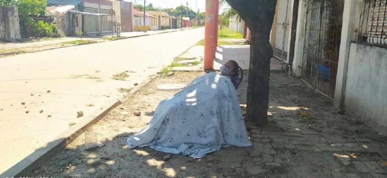 Mulher é deixada na calçada, em frente de sua casa, depois de apresentar sintomas de coronavírus - Reprodução/El Deber