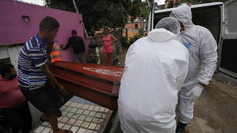 Trabalhadores funerários carregam o caixão de uma mulher que morreu de covid-19 em casa, em Manaus - BRUNO KELLY/REUTERS