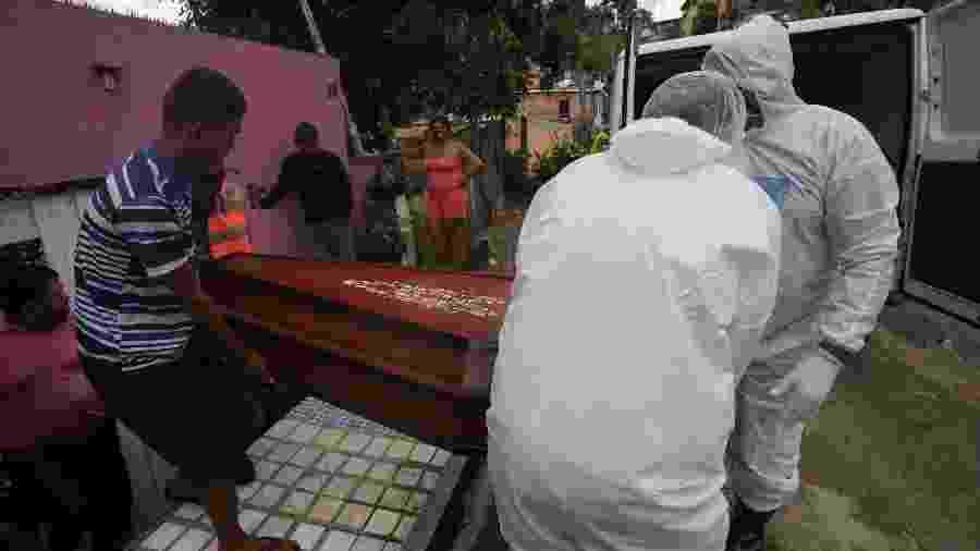Trabalhadores funerários vestindo roupas de proteção carregam o caixão de uma mulher que morreu da doença por coronavírus (COVID-19), de sua casa, em Manaus, - BRUNO KELLY/REUTERS