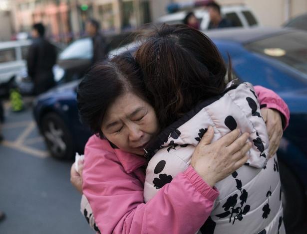7.mar.2016 - Parentes chineses de passageiros do voo MH370 da Malaysia Airlines, desaparecido em 8 de março de 2014, se abraçam na saída de fórum em Pequim