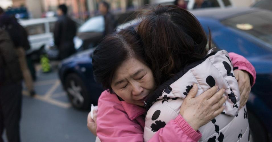 7.mar.2016 - Parentes chineses de passageiros do voo MH370 da Malaysia Airlines, desaparecido em 8 de março de 2014, se abraçam na saída de fórum em Pequim. O segundo aniversário de desaparecimento da aeronave marca o limite legal para a justiça chinesa aceitar ações de indenização contra a companhia aérea