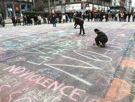 22.mar.2016 - Pessoas começam a escrever no chão de praça em Bruxelas mensagens de apoio e solidariedade às vítimas dos ataques terroristas coordenados na capital da Bélgica