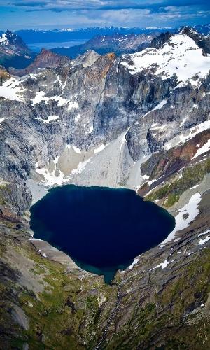 20.abr.2016 - Um lago glacial remoto cercado de picos de gelo e cobertos de neve no arquipélago Tierra del Fuego, na Argentina. A topografia do Tierra del Fuego é variada, incluindo altos picos e floresta temperadas