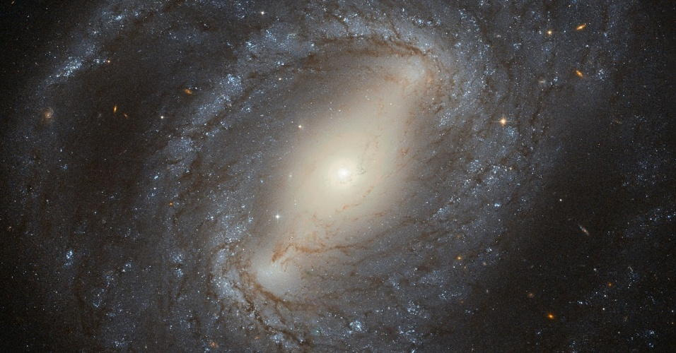 ESPIRAL ENIGMÁTICO - Descoberto em 1784 pelo astrônomo alemão-britânico William Herschel, NGC 4394 é uma galáxia espiral barrada situada a cerca de 55 milhões de anos-luz da Terra. A galáxia encontra-se na constelação de Coma Berenices (Cabeleira de Berenice). Seus braços espirais luminosos emergem das extremidades de uma barra que corta a parte central da galáxia. Estes braços são recheados com estrelas jovens azuis e filamentos escuros de poeira cósmica. Há no seu centro uma região de gás ionizado que intriga os cientistas. Não se sabe se o que há ali é fruto da influência de um buraco negro ou de um elevado nível de formação de estrelas