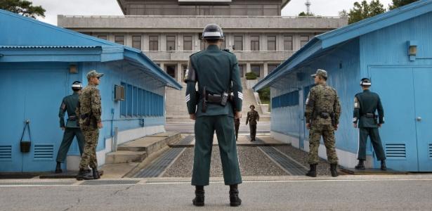 Soldados sul-coreanos (na frente) olham em direção ao lado norte-coreano enquanto um soldado da Coreia do Norte se aproxima