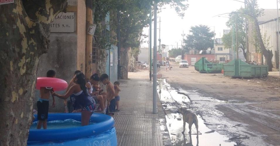 Crianças brincam em piscina de plástico na Villa 31; metade da população local é de imigrantes