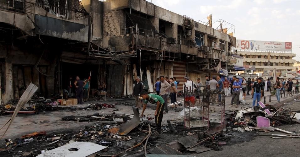 22.jul.2015 - Populares retornam ao local onde um carro-bomba foi detonado em Bagdá, no Iraque. O país foi alvo de quatro ataques terroristas com carros-bomba nesta terça-feira (21), todos atribuídos ao grupo terrorista Estado Islâmico (EI). Pelo menos 30 pessoas morreram e outras 81 ficaram feridas. O Iraque vive desde junho de 2014 uma guerra contra o EI, que conquistou amplas partes do território do país