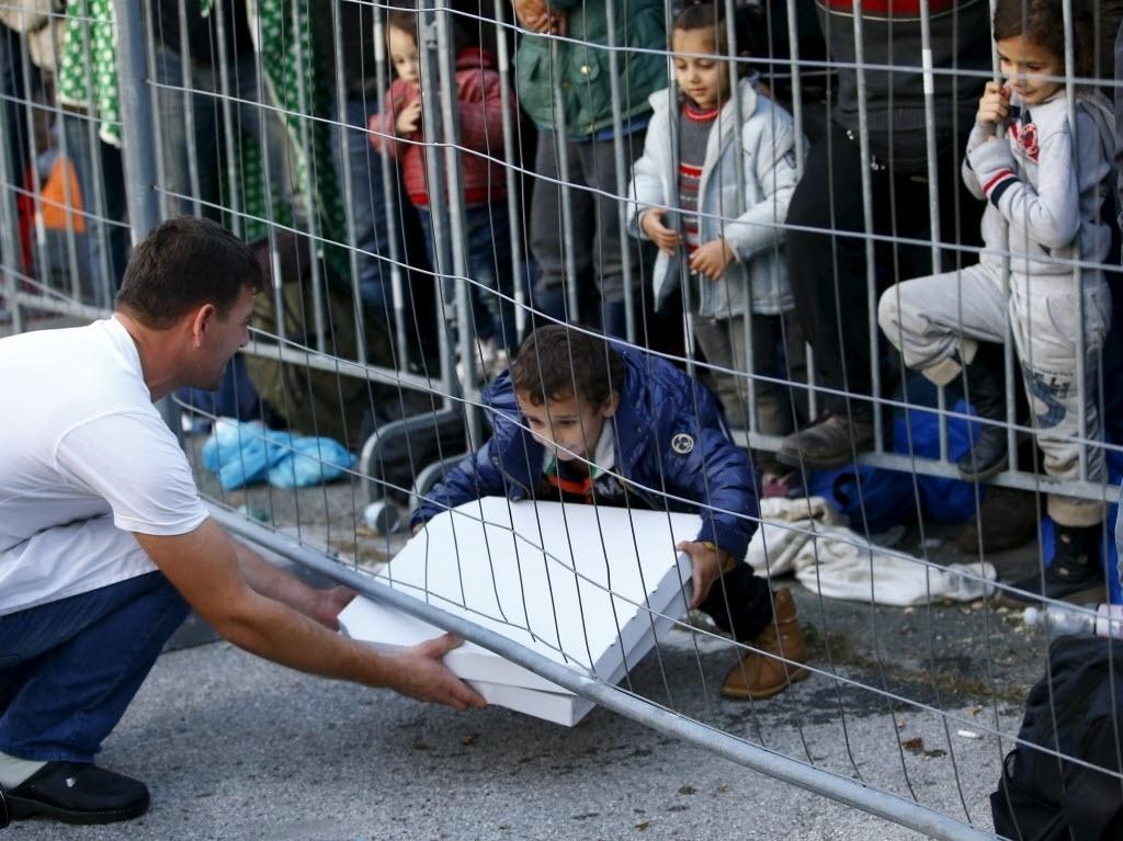 27.out.2015 - Garçom entrega pizza para um grupo de refugiados na fronteira entre Eslovênia e Áustria. A Eslovênia pretende convocar empresas privadas de segurança para ajudar a gerenciar o fluxo de milhares de imigrantes que atravessam o país em direção ao norte da Europa