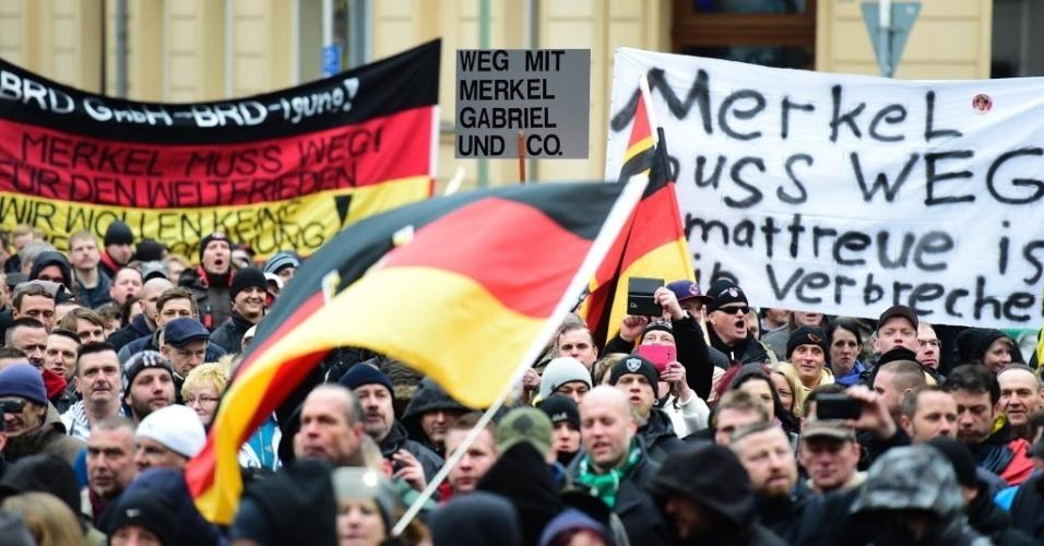 """12.mar.2016 - Manifestantes de extrema-direita fazem protesto contra o acolhimento de refugiados pela Alemanha, que eles chamam de """"invasão de imigrantes"""", em Berlim, neste sábado (12). Eles seguram cartazes e faixas com frases críticas à primeira-ministra Angela Merkel, como """"Merkel deve sair"""""""