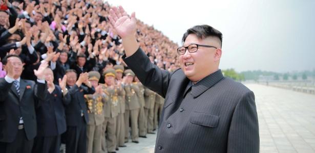 26.jun.2016 - O ditador norte-coreano Kim Jong-un acena para público durante uma sessão de fotos com oficiais envolvidos com sucesso do lançamento do míssil Hwasong-10