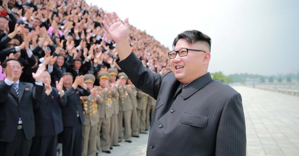 26.jun.2016 - O ditador norte-coreano Kim Jong-un acena para público durante uma sessão de fotos com oficiais envolvidos com sucesso do lançamento do míssil Hwasong-10, em imagem divulgada pela Agência Central de Notícias da Coreia do Norte