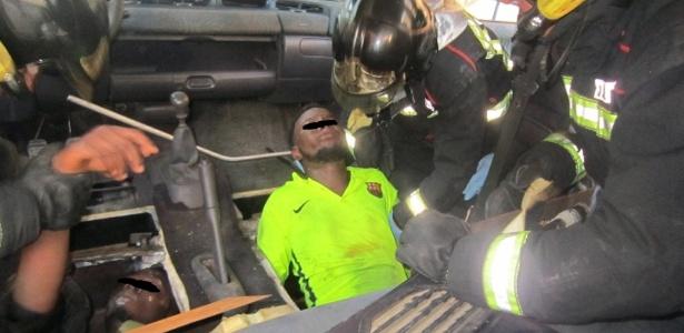 Guarda Civil Espanhola mostra bombeiros retirando migrantes africanos sob o fundo falso debaixo de assento de carro, em Melilla, Espanha