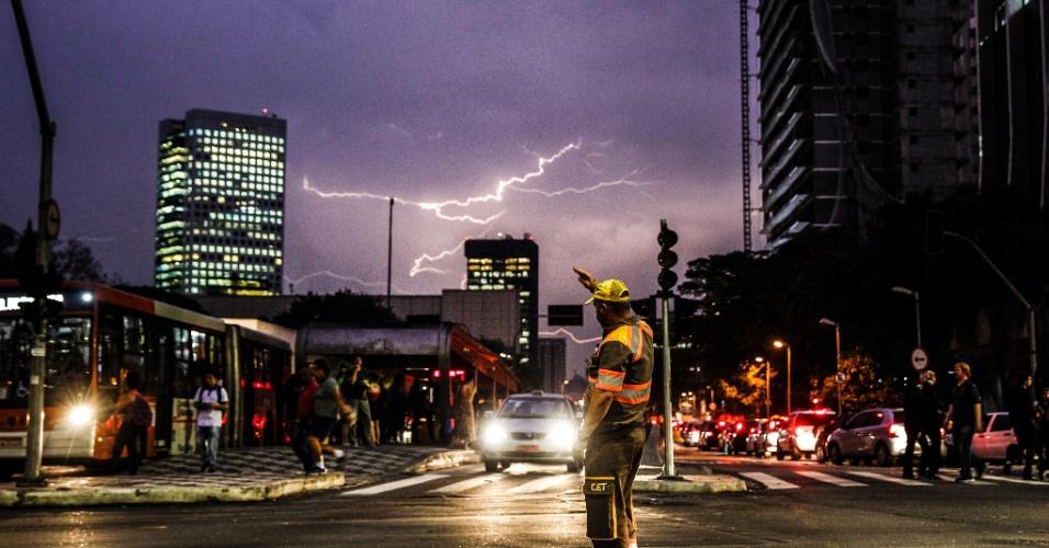 20.out.2016 - Agente de trânsito controla o tráfego no cruzamento das avenidas Brigadeiro Faria Lima com Rebouças, em Pinheiros, zona oeste de São Paulo, após semáforos pararem de funcionar por causa da forte chuva que caiu na capital paulista