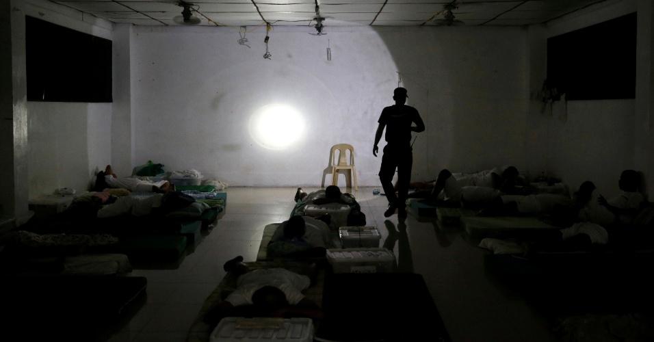 30.set.2016 - Guarda faz ronda enquanto usuários de drogas dormem em dormitório do Centro de Reabilitação de Usuários de Drogas Central Luzon, na província de Pampanga, nas Filipinas