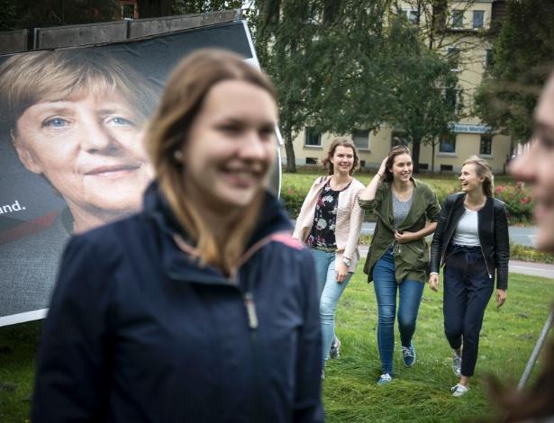 Mulheres andam ao lado de cartaz com Angela Merkel, em Osnabrück, na Alemanha
