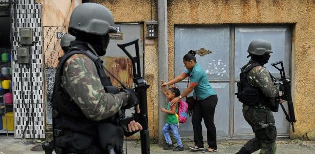 23.fev.2018 - Mulher e criança passam ao lado de militares em patrulha na favela da Vila Kennedy
