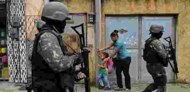 23.fev.2018 - Mulher e criança passam ao lado de militares em patrulha na favela da Vila Kennedy - Carl de Souza/AFP Photo
