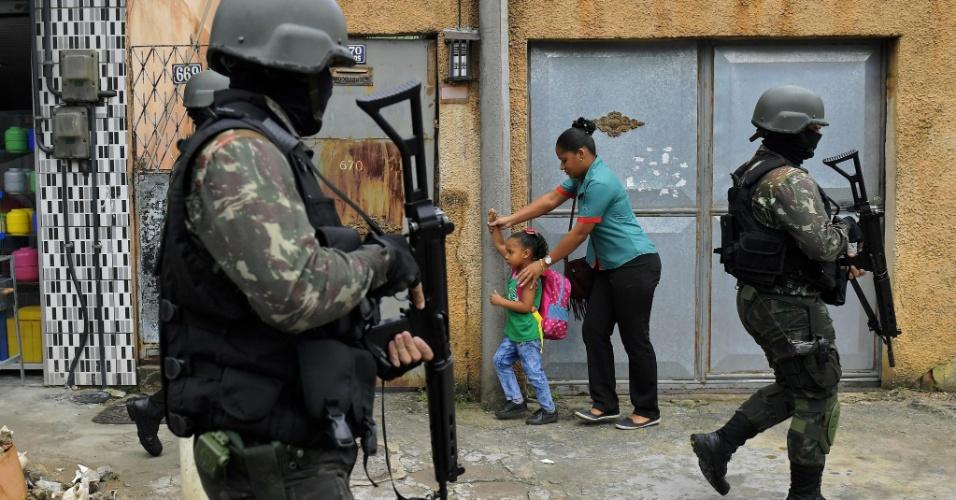 23.fev.2018 - Mulher e criança passam ao lado de militares em patrulha na favela da Vila Kennedy, no Rio de Janeiro