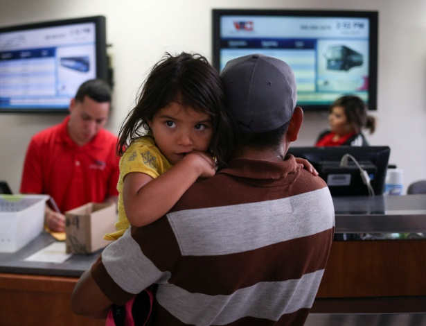 Pai imigrante de El Salvador e sua filha de três anos de idade são liberados da detenção nesta sexta-feira (27), junto com outras famílias, em McAllen, no estado do Texas - Loren Elliott/Reuters