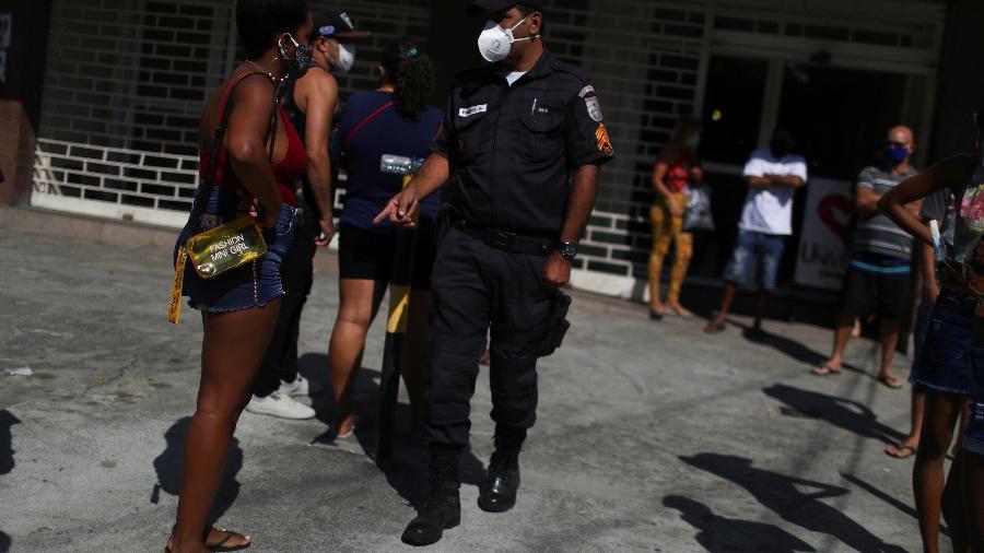 Um policial usando máscara fala com uma mulher fora do banco da Caixa, enquanto as pessoas esperam para receber ajuda emergencial do governo federal no Rio de Janeiro - PILAR OLIVARES/REUTERS