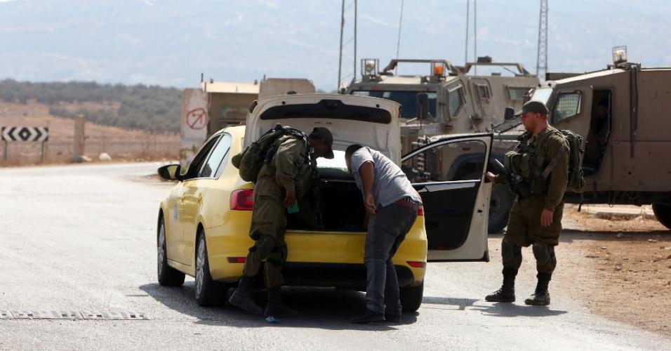 2.out.2015 - Soldados israelenes inspecionam carro de palestino em posto de controle perto de Beit Furik, uma área da Cisjordânia ocupada na qual estão localizadas algumas colônias. Centenas de soldados de Israel participam da busca pelos responsáveis pela morte de um casal de colonos, na presença de seus quatro filhos, de acordo com o Exército