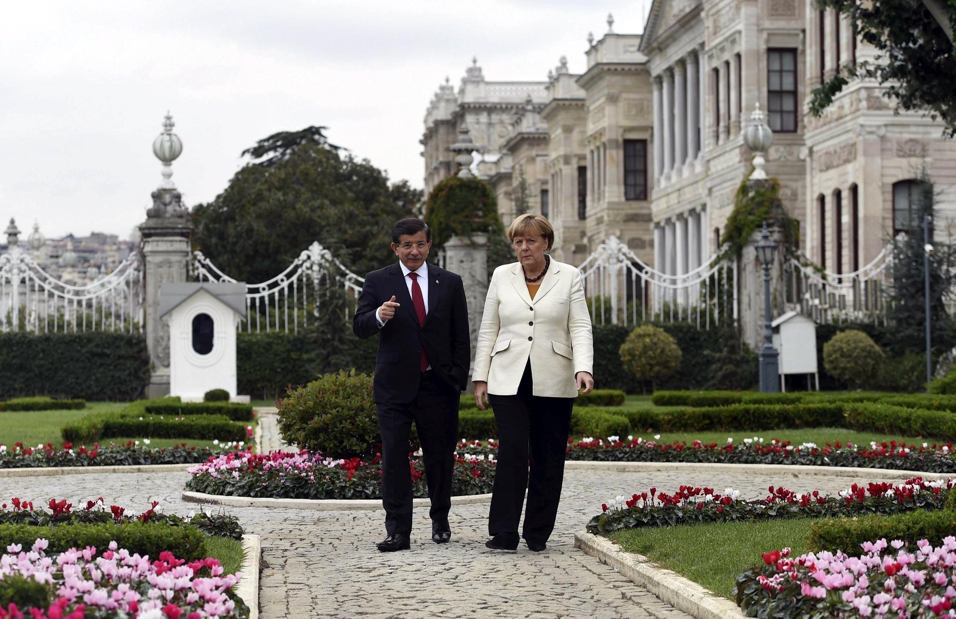 18.out.2015 - Chanceler alemã, Angela Merkel, caminha com o primeiro-ministro da Turquia, Ahmet Davutoglu, em Istambul. Ela está no país e, em troca da cooperação para conter o fluxo de refugiados em direção à Europa, ofereceu respaldo ao processo de adesão da Turquia à UE e ajuda financeira para país manter campos de refugiados