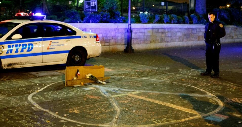 14.nov.2015 - Policial em Nova York observa homenagens às vítimas dos atentados de Paris, neste sábado (14)