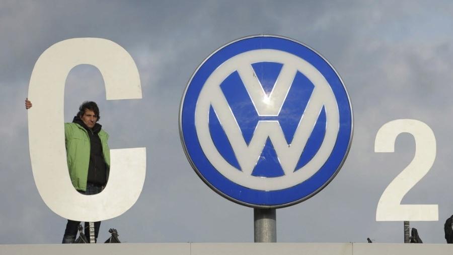 Ativista do Greenpeace protesta ao lado do logotipo da Volkswagen na fábrica da empresa de Wolfsburg, na Alemanha - Peter Steffen/Efe
