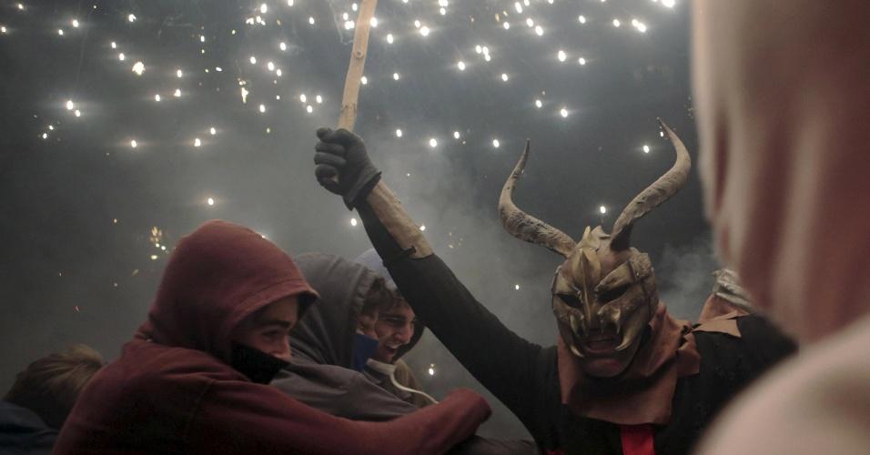 """24.jan.2016 - Um folião fantasiado de diabo com um fogo de artifício na mão participa do encerramento das festividades do """"Correfocs"""", em Palma, na Espanha. O festival é tradicionalmente celebrado no leste da Espanha, com pessoas fantasiadas como diabos dançantes enquanto acendem fogos de artifícios na frente de vários espectadores"""