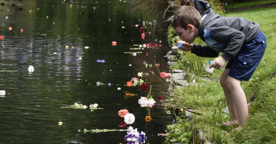 22.fev.2016 - Criança faz bolhas de sabão diante de várias flores lançadas no rio Avon, no Jardim Botânico de Christchurch, na Nova Zelândia, durante homenagem às vítimas do terremoto que atingiu a cidade há cinco anos e deixou 185 mortos