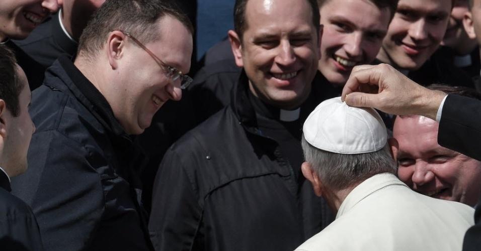 12.mar.2016 - Na foto, a mão de um homem aparece mexendo no solidéu do papa Francisco, após missa na praça de São Pedro, no Vaticano