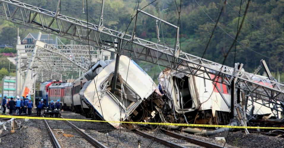 22.abr.2016 - Trabalhadores ferroviários tentam colocar de volta nos trilhos uma composição de passageiros que descarrilou próximo à cidade portuária de Yeosu (Coreia do Sul). O maquinista do trem morreu e oito passageiros ficaram feridos no acidente