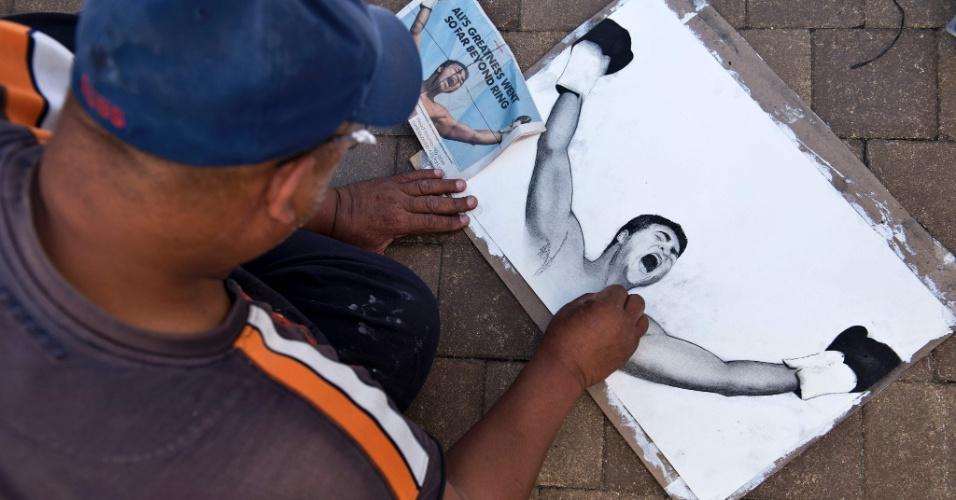 9.jun.2016 - Homem faz desenho de Muhammad Ali em frente ao Freedom Hall, em Louisville (EUA), local onde acontece o funeral do ex-boxeador. Ali morreu na última sexta-feira aos 74 anos, em consequência dos problemas de saúde derivados de uma batalha contra o Mal de Parkinson