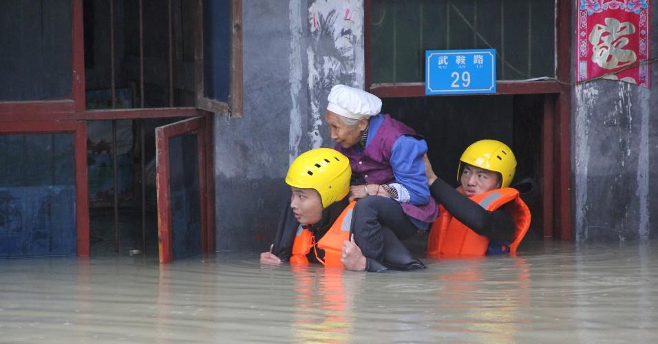 29.jun.2016 - Equipe de resgate retira idosa de dentro de um imóvel inundado em Chongqing, China