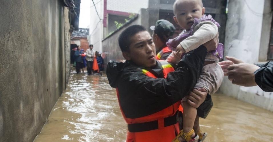 2.jul.2016 - Equipes de resgate retiram uma criança de uma casa alagada após o rompimento de um dique em Xinzhou, no distrito de Wuhan (China), neste sábado (2). O rompimento do dique aconteceu após uma forte chuva cair sobre a região central da China. Mais de 700 socorristas foram enviados para ajudar nos resgates de pessoas ilhadas
