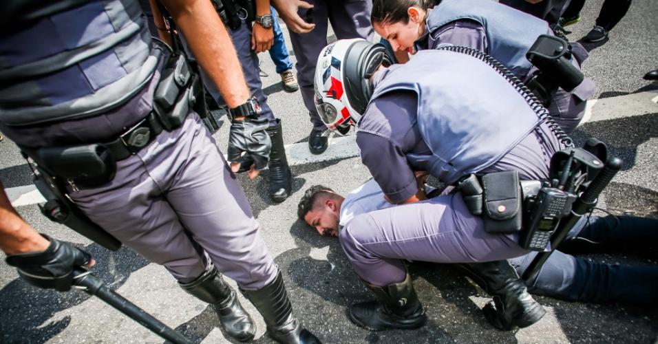 29.out.2016 - Policial detém manifestante durante ato na avenida Paulista, em São Paulo