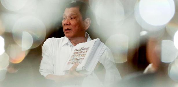 O presidente filipino Rodrigo Duterte mostra lista com policiais e políticos que estariam envolvidos com drogas ilegais, durante fórum em Manila