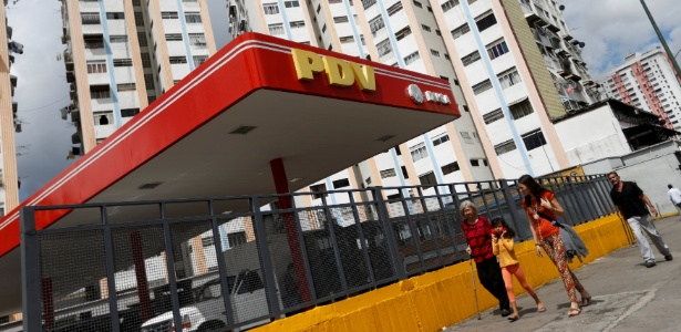 27.jul.2017 - Pedestres passam por posto da PDVSA em Caracas, na Venezuela