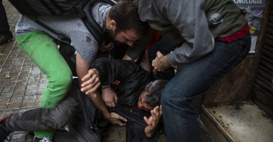 1º.out.2017 - Pessoas ajudam homem ferido por uma bala de borracha por policiais espanhóis do lado de fora de Ramon Llull, um dos locais de votação em Barcelona