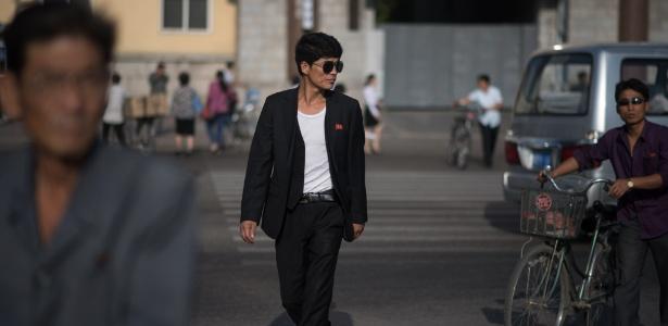 Homem atravessa a rua na região da estação central de trem de Pyongyang, na Coreia do Norte