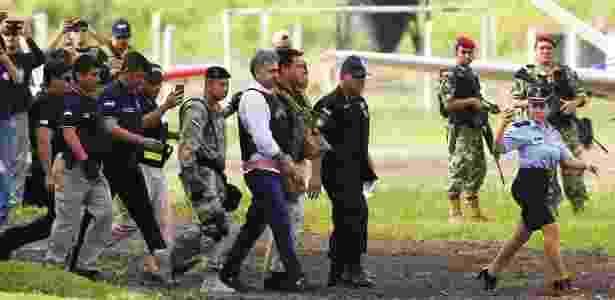 Narcotraficante Jarvis Chimenes Pavão é escoltado pela Polícia Federal brasileira no aeroporto de Luque, no Paraguai, para ser extraditado ao Brasil - Jorge Saenz/AFP